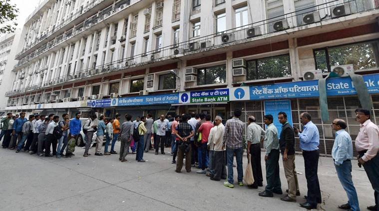 New Delhi: People queue up at out side of banks ATM to get money in New Delhi on Sunday. PTI photo by Vijay Verma(PTI11_13_2016_000071A)